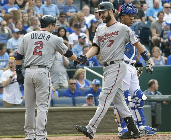 The Minnesota Twins' Brian Dozier (2) greets Joe Mauer in front of Kansas City Royals catcher Salvador Perez after Mauer's first-inning two-run home r