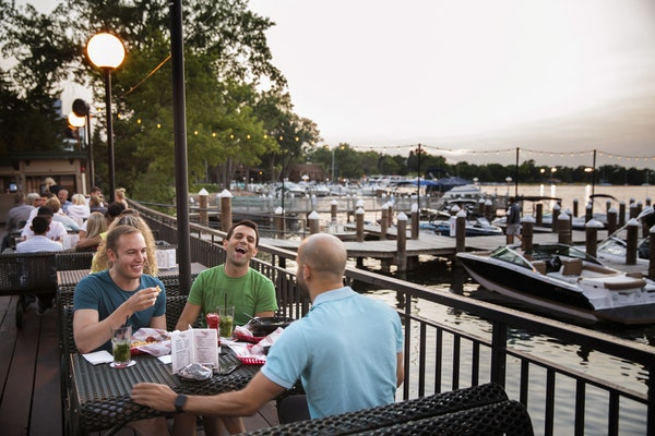 Clockwise from left, Isaac Bar and Tyler Smith, both of Minneapolis, and Micah Berman of St. Louis Park enjoyed the sprawling patio at Maynard's in