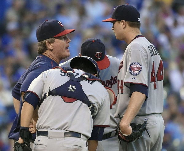 Minnesota Twins pitching coach Neil Allen makes a visit to the mound to talk with starting pitcher Kyle Gibson (44) in the fourth inning against the K