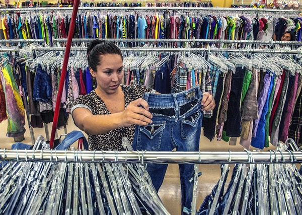 A woman shops for used clotting at a Savers thrift store.