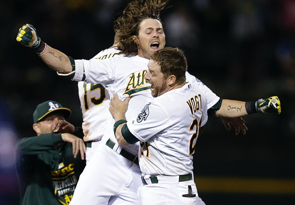 Oakland Athletics' Stephen Vogt (21) and Josh Reddick celebrate after Vogt drove in the winning run against the Minnesota Twins in the 10th inning of