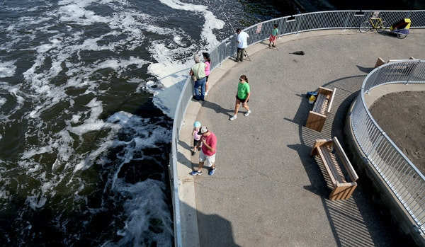 Pedestrians checked out the reopened Coon Rapids Dam viewing areas. Work to shore up the dam and install barriers to invasive carp is 95 percent done.