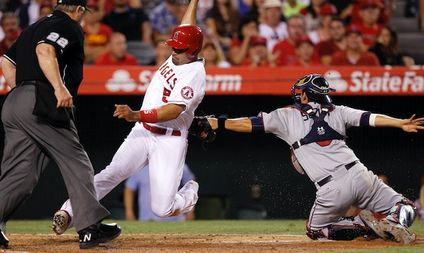 Los Angeles Angels designated hitter Albert Pujols (5) is safe at the plate as Minnesota Twins catcher Kurt Suzuki, right, doesn't hold onto the throw