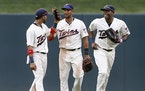Eddie Rosario, Aaron Hicks and Torii Hunter celebrate their 9-5 win over the Detroit Tigers on Saturday.