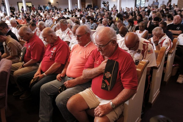 Supporters bow their heads in prayer for the start of an interfaith vigil at Olivet Baptist Church held in remembrance of victims of the July 16 shoot