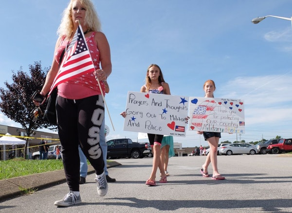 Crissy Essex, left, 44, Sabrina Cupell, and Cheyenne Essex bring signs and an American flag to a memorial near where a gunman fired shots into the Arm