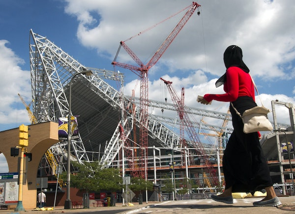 The new Vikings stadium is millions over budget, leading to some tense, closed-door meetings.