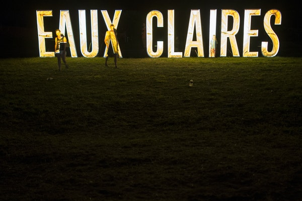 Festival goers walked along the illuminated Eaux Claires sign Saturday night during Bon Iver's set.