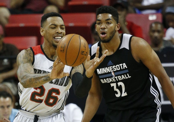 Portland Trail Blazers' Malcolm Thomas passes around Minnesota Timberwolves' Karl-Anthony Towns during the first half of an NBA summer league basket