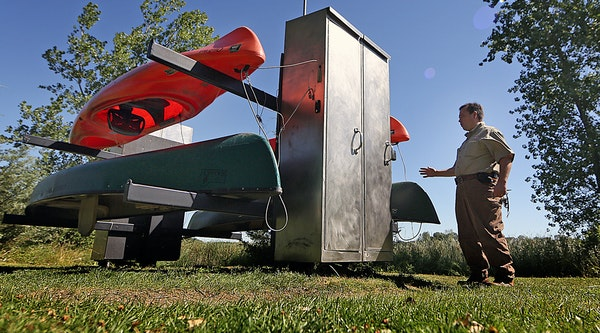 Service technician R. David Corbet checked the kiosk that holds two canoes and two kayaks that are free for Anoka County residents to use on Sunfish L
