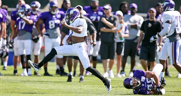 Cornerback Shaun Prater high stepped away from Chase Ford after intercepting a pass during Vikings training camp at Minnesota State University Mankato