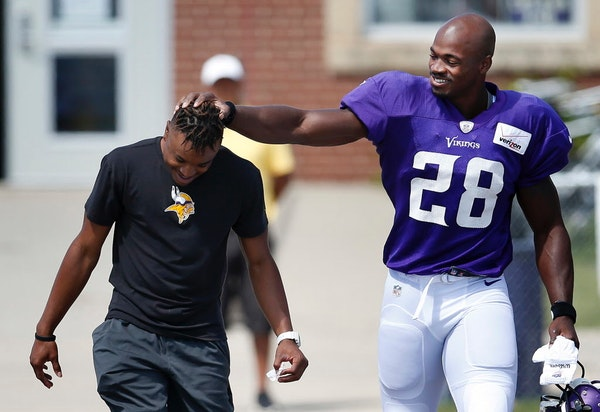 Vikings running back Adrian Peterson joked with equipment assistant E.J. Johnson before a practice on Aug. 11.