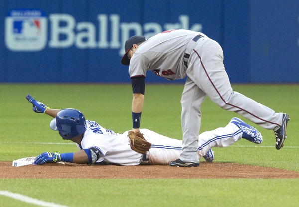 Toronto Blue Jays' Edwin Encarnacion is safe on a double as Minnesota Twins' Brian Dosier comes down late with the tag during the first inning of