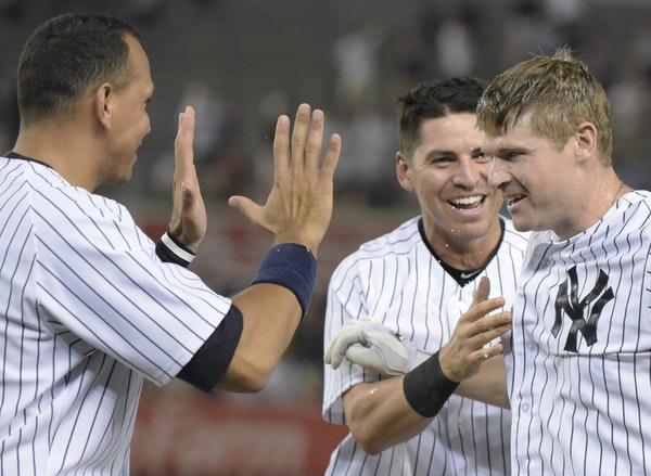 New York Yankees' Chase Headley, right, celebrates with Jacoby Ellsbury and Alex Rodriguez, left, after the winning run scored as Headley grounded o