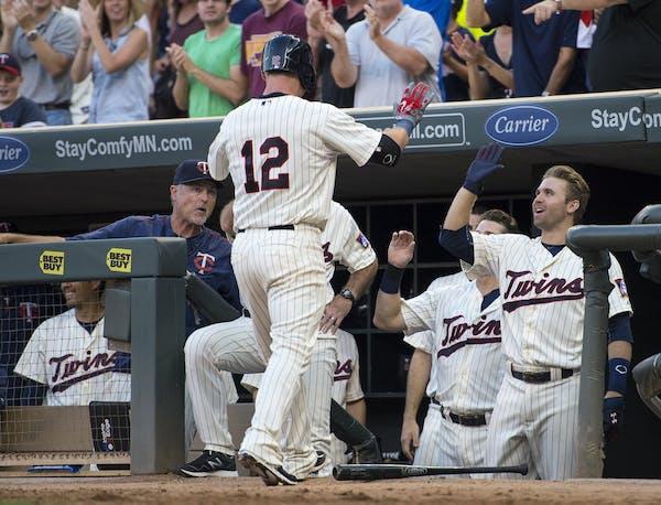 Minnesota Twins catcher Chris Herrmann (12) high fived second baseman Brian Dozier (2) after Herrmann hit a homer against the Cleveland Indians at Tar