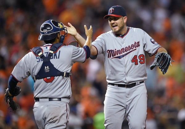 Minnesota Twins relief pitcher Kevin Jepsen (49) celebrates with catcher Kurt Suzuki, left, after the Twins defeated the Baltimore Orioles 3-2 in a ba