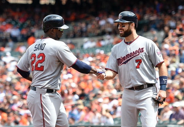 Minnesota Twins' Miguel Sano (22) is greeted by Joe Mauer (7) at home after Sano hit a two-run home run against the Baltimore Orioles during the first