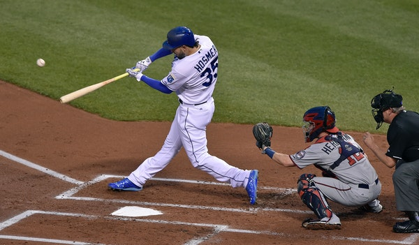The Kansas City Royals' Eric Hosmer (35) connects on a three-run double in the first inning in front of Minnesota Twins catcher Chris Herrmann (12) on