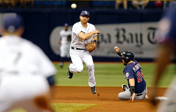 Tampa Bay Rays second baseman Logan Forsythe follows through on a throw to first past a sliding Minnesota Twins' Trevor Plouffe to complete the double
