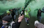 """Members of the Emerald City Supporters burn smoke devices as they take part in the traditional """"March to the Match"""" before the Seattle Sounders face S"""