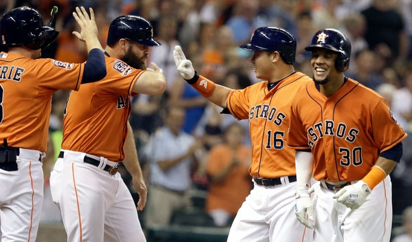 Houston Astros' Hank Conger (16) celebrates his grand slam with Jed Lowrie, left, Evan Gattis and Carlos Gomez (30) in the fourth inning of a baseball