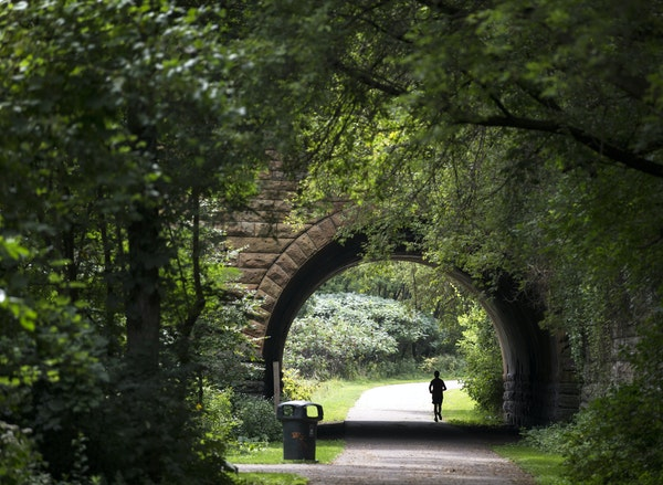 The biking and hiking paths in Swede Hollow Park are set in a secluded valley. Here, a jogger passed under the E. 7th Street bridge.