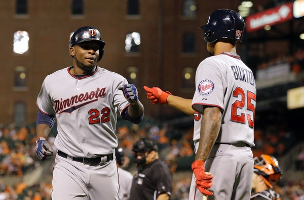 Minnesota Twins' Miguel Sano, left, fist-bumps teammate Byron Buxton after scoring on a bases-loaded walk to Eduardo Nunez during the fourth inning of