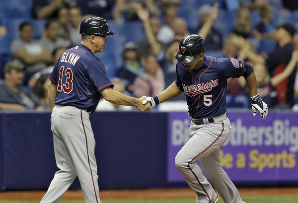 Minnesota Twins' Eduardo Escobar (5) shakes hands with third base coach Gene Glynn after his home run off Tampa Bay Rays starting pitcher Chris Arch