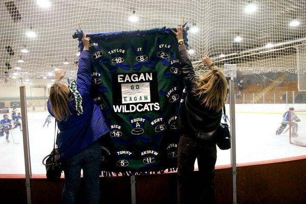 Eagan hockey moms hang a banner before a squirt hockey game at the Fargo Coliseum in February 2007.