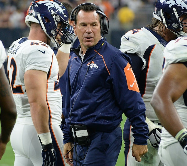 Denver Broncos head coach Gary Kubiak, center, talks to his players during the first half of an NFL preseason football game against the Houston Texans