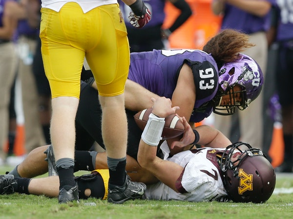 Minnesota quarterback Mitch Leidner (7) takes a hard hit from TCU defensive end Mike Tuaua (93) during the second half of an NCAA college football gam