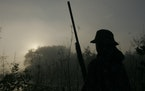 Sam Olson, 14, of Minnetonka, scans the sky for ducks at dawn during Youth Waterfowl Day at the Minnesota Valley National Wildlife Refuge near Shakope