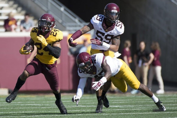 University of Minnesota running back Rodney Smith (24) breaks past defenders Adekunle Ayinde (45) and Ray Dixon (59) during the first half of a spring