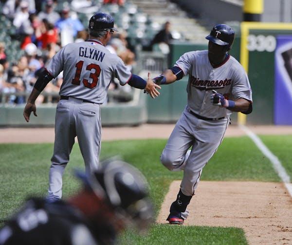 Minnesota Twins' Torii Hunter, right, high-fives third base coach Gene Glynn (13) after hitting a three-run home run in the first inning of a baseball