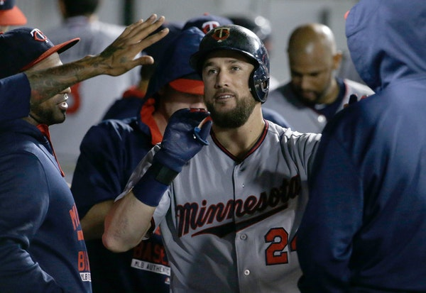 Minnesota Twins' Trevor Plouffe celebrates with teammates after hitting a solo home run against the Chicago White Sox during the eighth inning of a ba