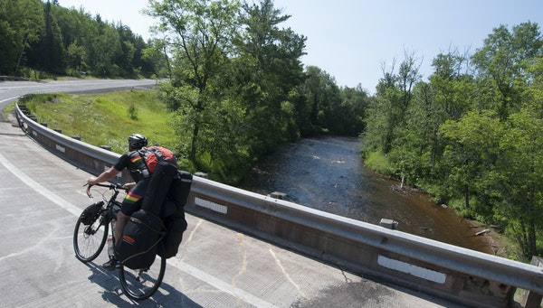 Ben Weaver rounded the corner over the Brule River on his bike trip tour.