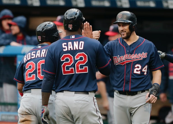 Minnesota Twins' Trevor Plouffe (24) congratulates Eddie Rosario (20) and Miguel Sano (22) after all three scored on a three-RBI double by Torii Hunte