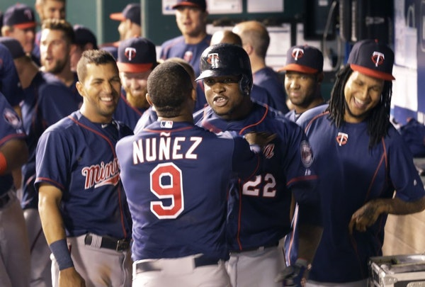 Minnesota Twins designated hitter Miguel Sano (22) is congratulated by teammate Eduardo Nunez (9) following his solo home run during the 12th inning.