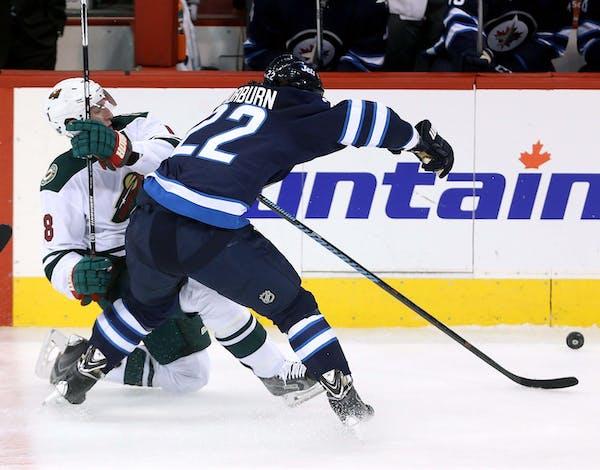 Winnipeg Jets' Chris Thorburn, right, hits Minnesota Wild's Ryan Carter during the first period of an NHL preseason hockey game Tuesday, Sept. 22, 201