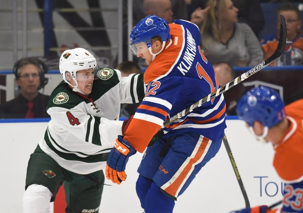 Minnesota Wild's Mike Reilly, left, and Edmonton Oilers' Rob Klinkhammer battle for the puck during the first period of an NHL preseason hockey game S
