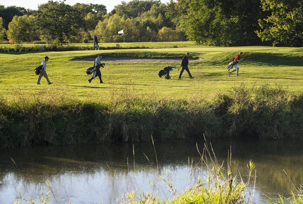 Golfers walked Hiawatha golf course near Pond E Wednesday. The golf course has not fully reopened since flooding in 2014.