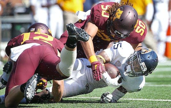 Minnesota's linebacker Cody Poock, left, and Minnesota's linebacker Jack Lynn stopped Kent State wide receiver Ernest Calhoun