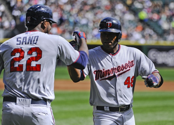 Minnesota Twins' Torii Hunter (48) high-fives designated hitter Miguel Sano (22) after hitting a three-run home run in the first inning of a baseball
