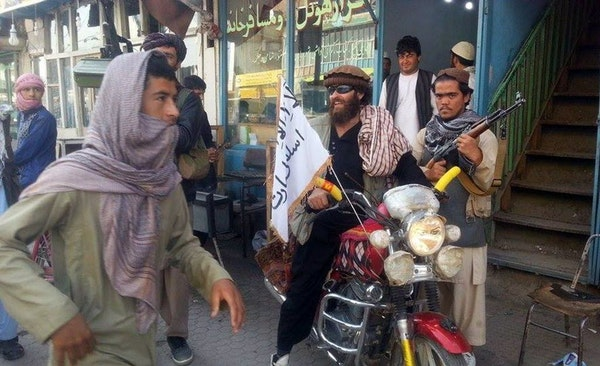 A Taliban fighter sits on his motorcycle adorned with a Taliban flag in a street in Kunduz, Afghanistan, Tuesday, Sept. 29, 2015.