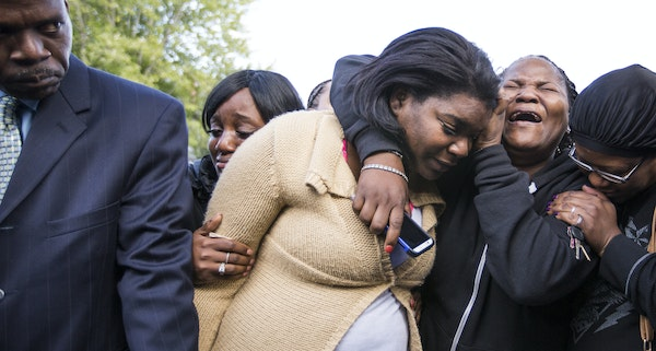 The mother of three children who died in a house fire, in center in beige, cries with her mother and aunt during a prayer vigil outside the home in Mi
