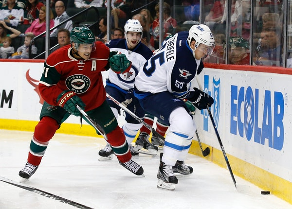 Minnesota Wild left wing Zach Parise (11) and Winnipeg Jets center Mark Scheifele (55) chase the puck during the second period of an NHL preseason hoc