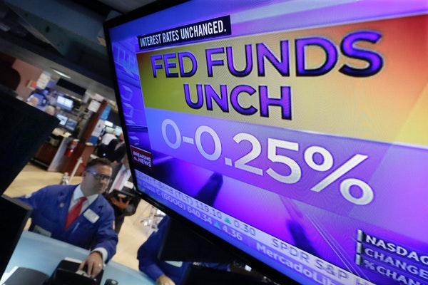 Specialist Paul Cosentino worked at his post on the floor of the New York Stock Exchange, as the decision of the Federal Reserve appeared on a televis