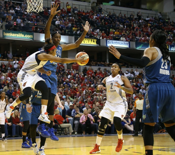 Indiana guard Briann January, off her feet but not off her game, dished around Lynx center Sylvia Fowles to cutting teammate Erlana Larkins (2).