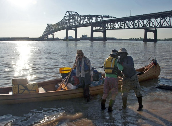 Near the Horace Wilkinson Bridge in an industrial stretch of Baton Rouge, La., members of an expedition on the Lower Mississippi River disembark from