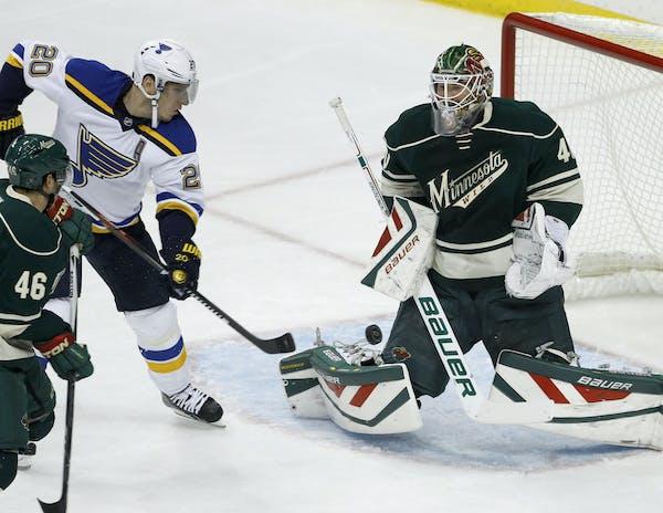 Minnesota Wild goalie Devan Dubnyk (40) deflects a shot by St. Louis Blues left wing Alexander Steen (20) in front of Wild defenseman Jared Spurgeon (